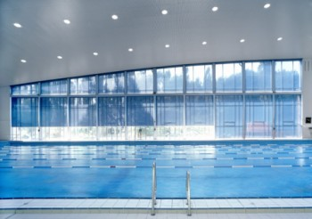 Wide vertical roller systems for the glass wall of a swimming pool